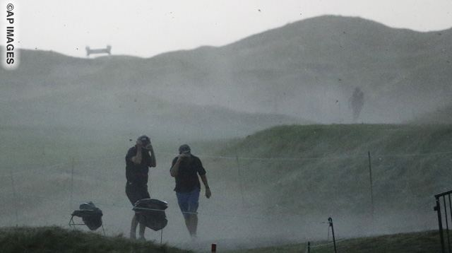 Fans scramble for cover near the first hole as a storm passes after play was suspended for weather during the second round of the PGA Championship golf tournament Friday, Aug. 14, 2015, at Whistling Straits in Haven, Wis. (AP Photo/Brynn Anderson)