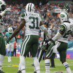 New York Jets' Darrelle Revis, right, celebrates after making an interception over Miami Dolphins' Jarvis Landry during the NFL football game between the New York Jets and the Miami Dolphins and at Wembley stadium in London, Sunday, Oct. 4, 2015. (AP Photo/Matt Dunham)