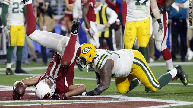 Arizona Cardinals wide receiver Larry Fitzgerald (11) scores the game winning touchdown in overtime as Green Bay Packers defensive end Mike Daniels (76) defends during the second half of an NFL divisional playoff football game, Saturday, Jan. 16, 2016, in Glendale, Ariz. The Cardinals won 26-20 in overtime. (AP Photo/Ross D. Franklin)
