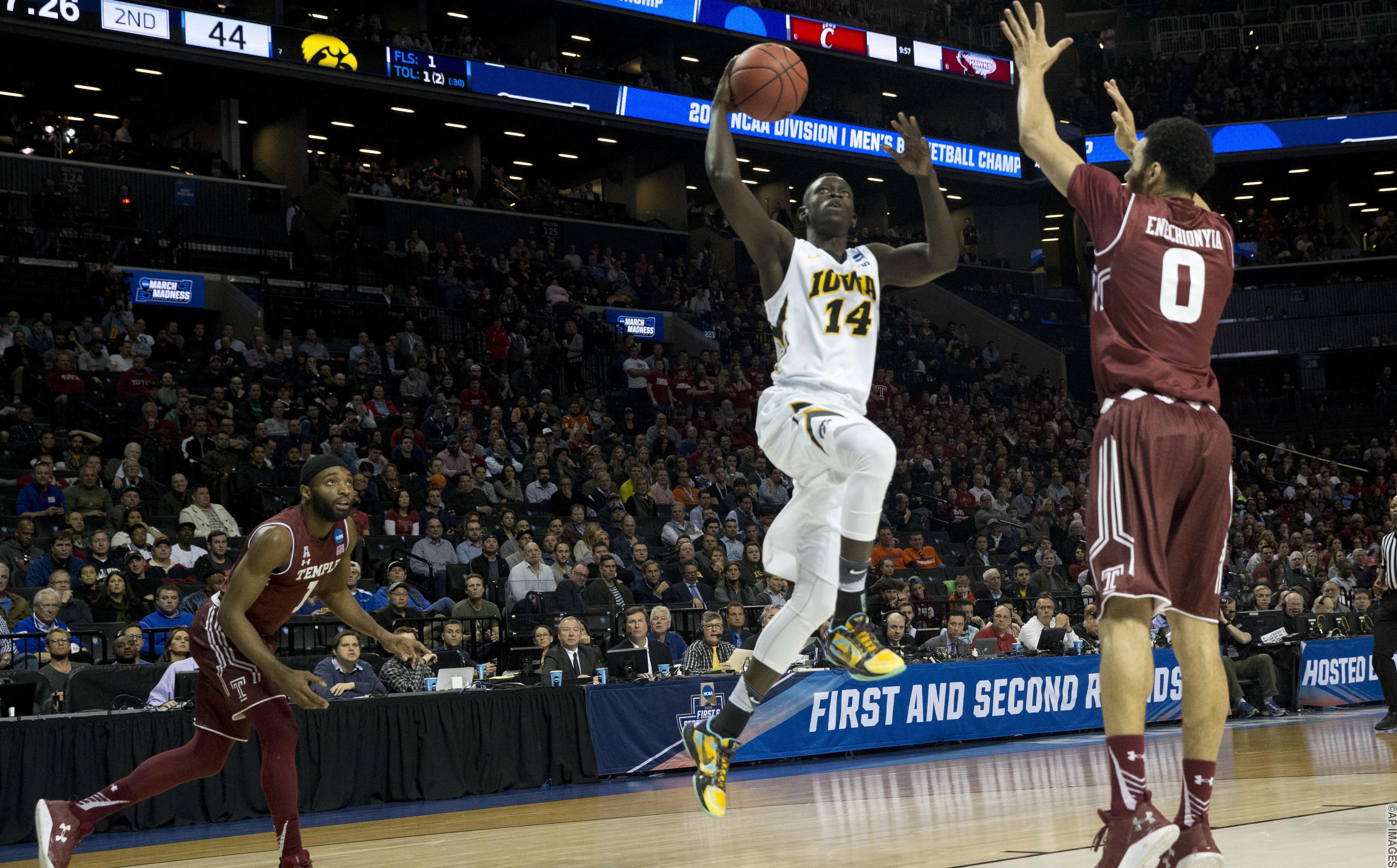 Iowa guard Peter Jok (14) goes to the basket past Temple forward Obi Enechionyia (0) and guard Josh Brown (1) during the second half of a first round men's college basketball game in the NCAA Tournament, Friday, March 18, 2016, in New York. Iowa won 72-20 in overtime. (AP Photo/Mary Altaffer)