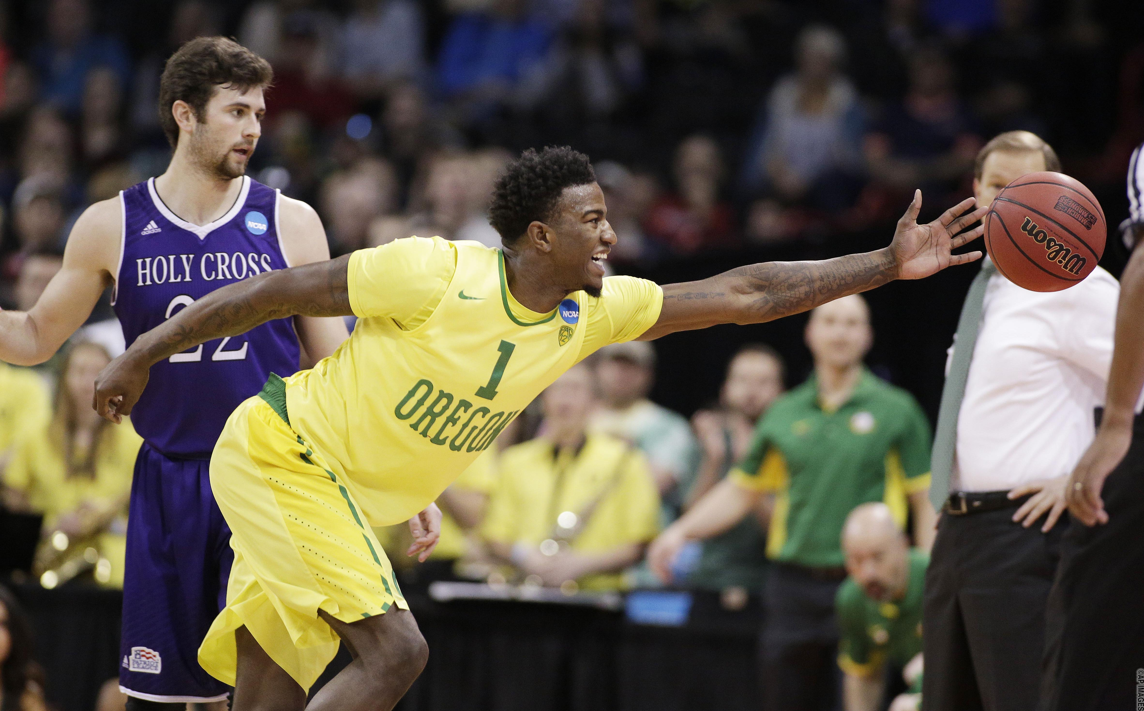 Oregon forward Jordan Bell (1) goes after a loose ball in front of Holy Cross guard Robert Champion (22) during the first half of a first-round men's college basketball game in the NCAA Tournament in Spokane, Wash., Friday, March 18, 2016. (AP Photo/Young Kwak)