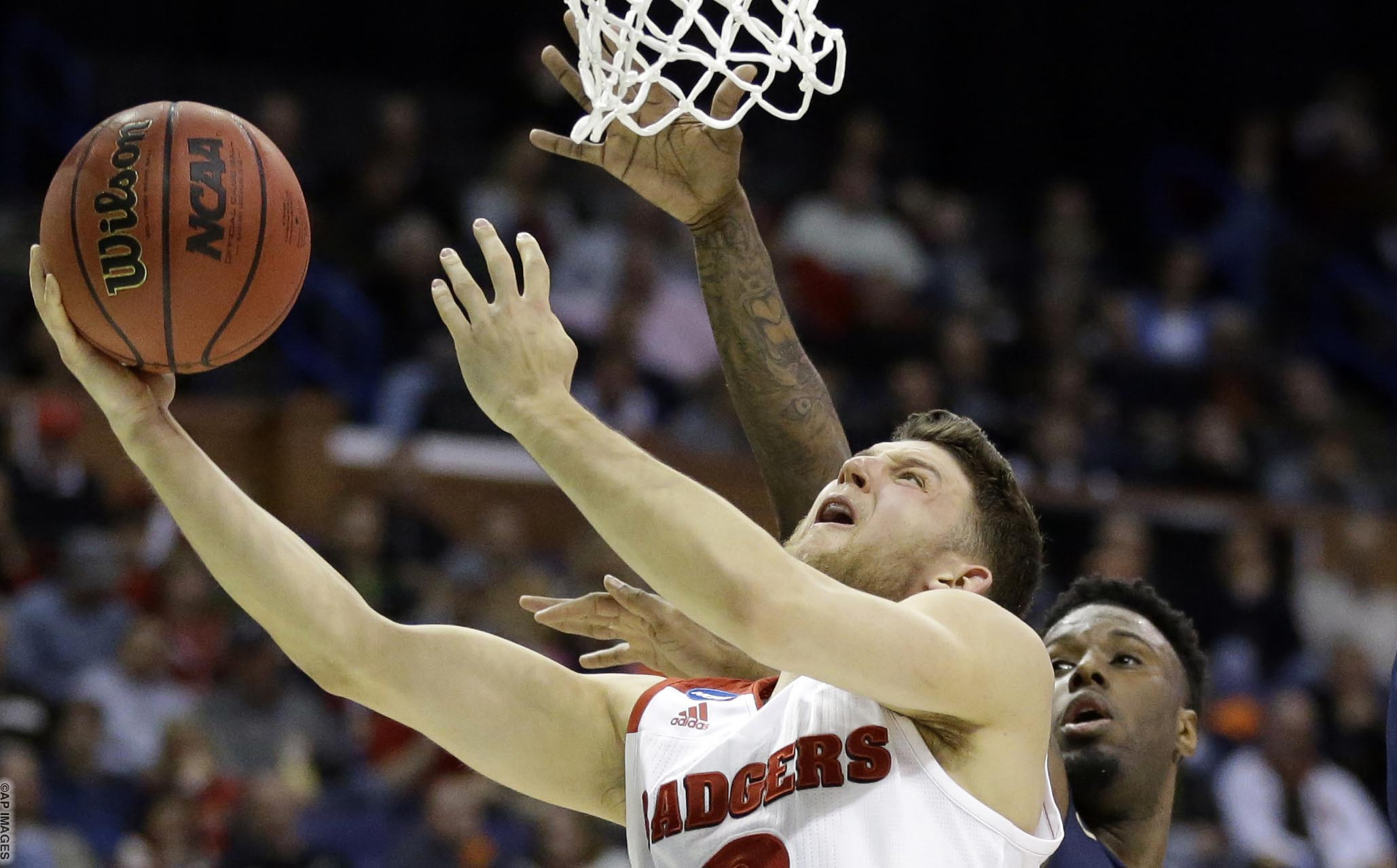 Wisconsin's Zak Showalter, left, heads to the basket as Pittsburgh's Jamel Artis defends during the first half of a first-round men's college basketball game in the NCAA tournament, Friday, March 18, 2016, in St. Louis. (AP Photo/Jeff Roberson)