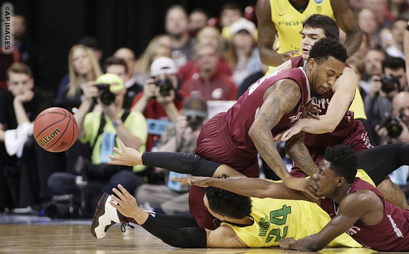 Oregon forward Dillon Brooks,center, goes after a loose ball against Saint Joseph's forward Isaiah Miles, left, guard Shavar Newkirk, right, and forward Pierfrancesco Oliva during the first half of a second-round men's college basketball game in the NCAA Tournament in Spokane, Wash., Sunday, March 20, 2016. (AP Photo/Young Kwak)