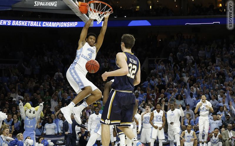 North Carolina's Isaiah Hicks, left, hangs on the rim after a dunk as Notre Dame's Steve Vasturia looks on during the second half of a regional final men's college basketball game in the NCAA Tournament, Sunday, March 27, 2016, in Philadelphia. (AP Photo/Chris Szagola)