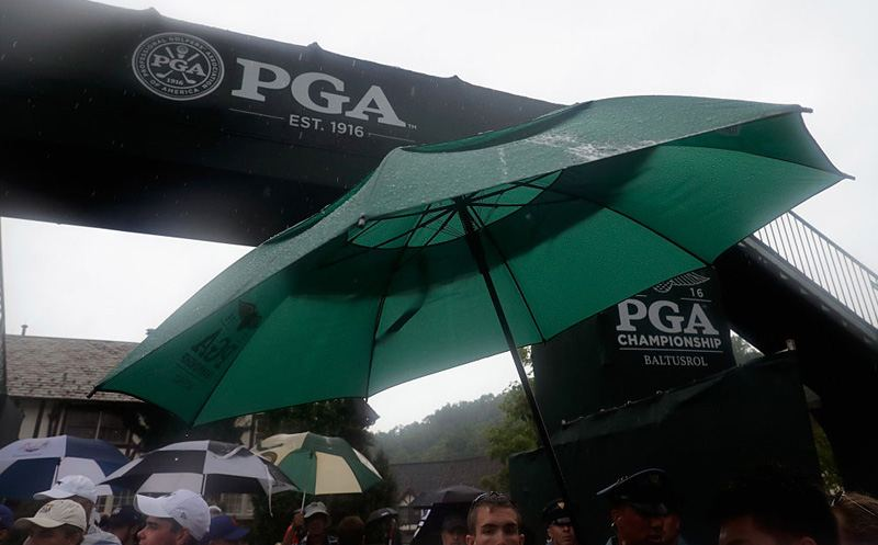 SPRINGFIELD, NJ - JULY 30: Fans take cover during a rain delay during the third round of the 2016 PGA Championship at Baltusrol Golf Club on July 30, 2016 in Springfield, New Jersey.  (Photo by Andy Lyons/Getty Images)