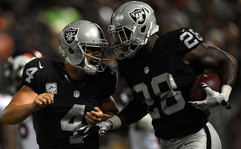 OAKLAND, CA - NOVEMBER 06:   Latavius Murray #28 and Derek Carr #4 of the Oakland Raiders celebrate after a touchdown against the Denver Broncos at Oakland-Alameda County Coliseum on November 6, 2016 in Oakland, California. (Photo by Thearon W. Henderson/Getty Images)
