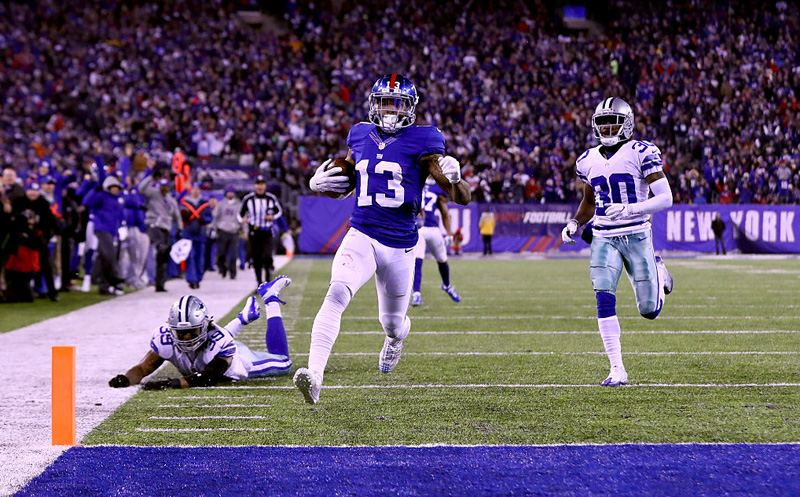 EAST RUTHERFORD, NJ - DECEMBER 11:  Odell Beckham Jr. #13 of the New York Giants scores a 61 yard touchdown against the Dallas Cowboys during the third quarter of the game at MetLife Stadium on December 11, 2016 in East Rutherford, New Jersey.  (Photo by Al Bello/Getty Images)